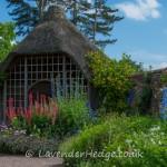 Summerhouse surrounded by flowers in walled garden